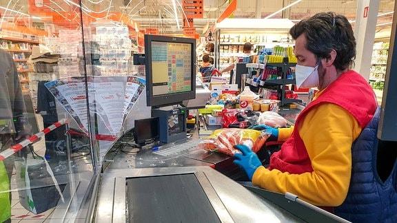 Ein Kassierer arbeitet mit Mundschutz in einem Supermarkt