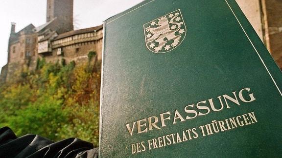 Ein Mann hält 1993 vor der Wartburg in Eisenach die Thüringer Verfassung in den Händen