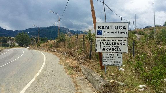 An einem Straßenrand stehen mehrere Schilder, auf einem der Schilder steht der Ortsname San Luca.
