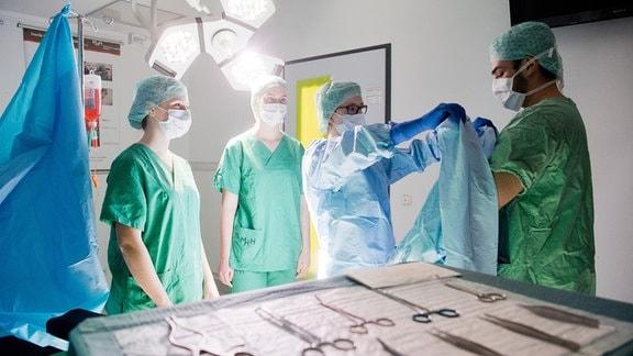 Medizinstudenten üben in einem nachgebildeten OP-Raum das Anlegen eines OP-Kittels.