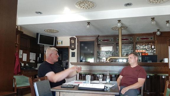 Zwei Männer sitzen an einem Tisch.