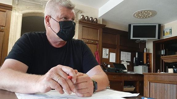 Ein Mann mit Maske sitzt an einem Tisch vor Unterlagen.