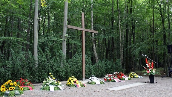 Niedergelegte Kränze vor Kreuz auf dem Trauerplatz