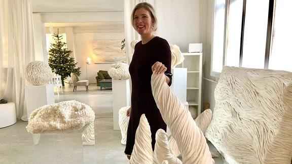 Eine Frau steht neben einem Kunstwerk.