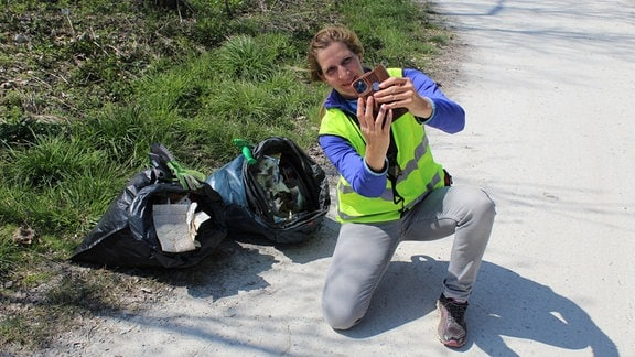 Eine Frau in gelber Weste sammelt am Straßenrand Müll auf.