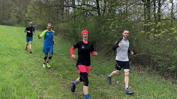 Vier Läufer auf einer Wiese.