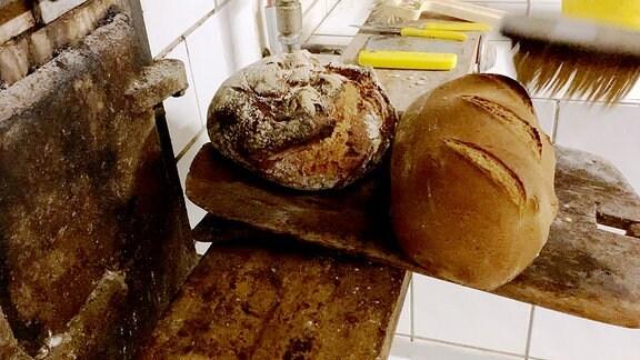 Frisch gebackenes Brot liegt auf einem Holzbrett