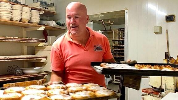 Ein Bäcker trägt zwei Bleche mit süßen Teilchen.