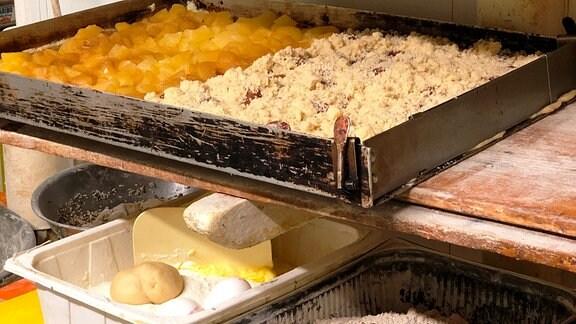 Verschiedene Teige und fertige Kuchen in einem Regal