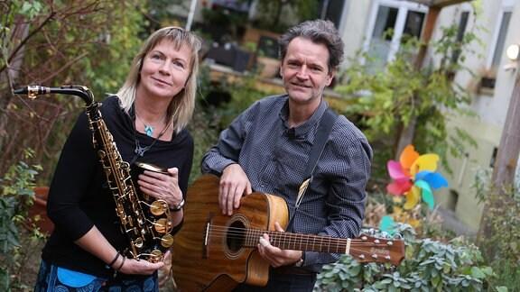 Eine Frau mit Saxofon und ein Mann mit Gitarre in einem Garten