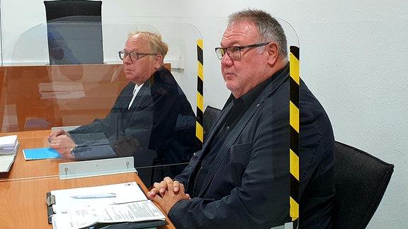 Zwei Männer sitzen in einem Gerichtssaal