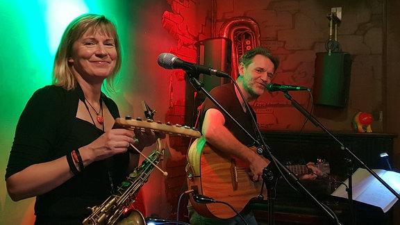Eine Saxofonistin und ein Gitarrist bei einem Konzert.
