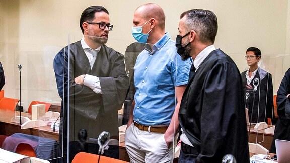 Mark Schmidt (Mitte) im Gespräch mit seinen zwei Anwälten hinter Plexiglas im Gericht.