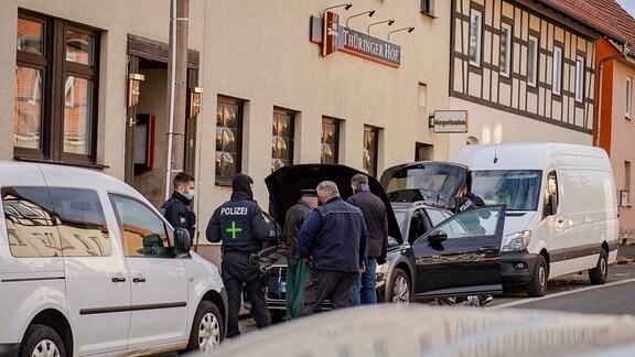 Polizeibeamter vor Gebäude bei Drogenrazzia