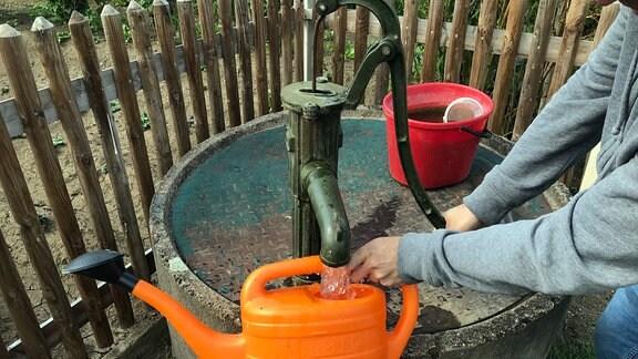 Aus einer Brunnenanlage vor Gartenzaun wird Wasser in eine orangefarbene Gießkanne gezapft