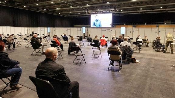 Menschen sitzen in der Messehalle verteilt auf Stühlen und warten auf ihre Impfung