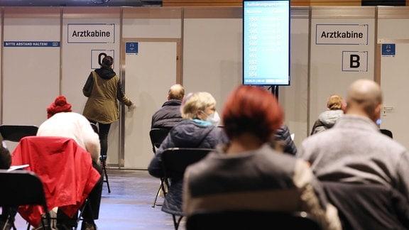 Eine Frau öffnet eine Tür, hinter ihr sitzen Menschen auf Stühlen