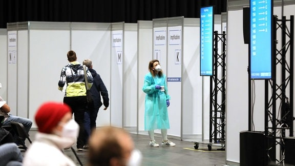 Eine Frau mit Schutzkittel schaut in einer Halle mit Impfkabinen auf Anzeigetafeln