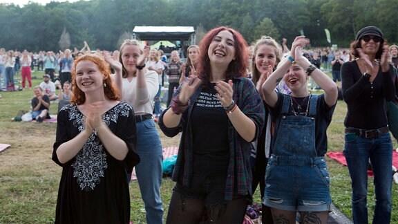 Konzertbesucher lachen und applaudieren.