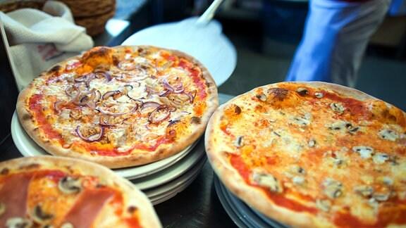 Fertige Pizzen auf Tellern