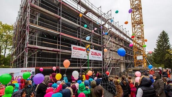 An einem großen Gebäude mit vielen Kindern davor wird eine Richtkrone aufgezogen.