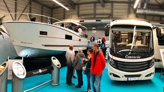 Besucher stehen auf der Messe Reisen und Caravan in Erfurt zwichen einem Boot und einem Campingbus.