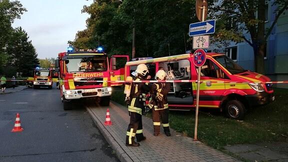 Zwei Feuerwehrautos stehen vor einem Wohnblock in Weimar-West. Hinter einem Absperrband stehen zwei Feuerwehrleute