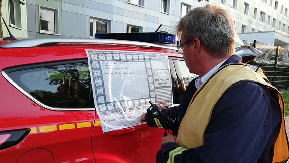 Ein Feuerwehrmann steht vor einem roten Pkw, an dessen Seite ein Schaubild angebracht ist