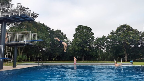 Badegäste probieren den neuen Sprungturm aus.