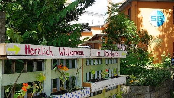 """Am Tor zum Stadtgarten steht auf einer Holzpalette: """"Herzlich Willkommen im Prachtgarten."""""""