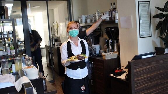 """Das Restaurant """"Cielo"""" in Weimar. Es stehen wenige Tische im Raum, am Boden sind Markierungen aufgeklebt, Menschen tragen Masken"""