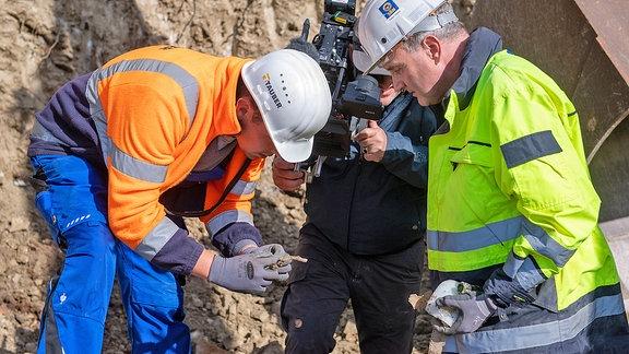 Zwei Männer in Arbeitskleidung und Helm stehen gebückt und betrachten ein Metallteil, daneben steht ein Mann mit einer Kamera auf der Schulter