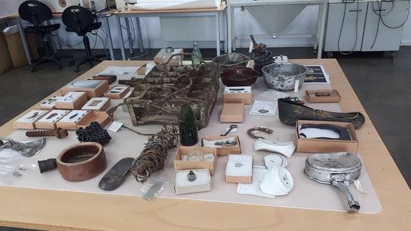 Konservierte Fundstücke aus dem ehemaligen Konzentrationslager liegen auf einem Tisch.