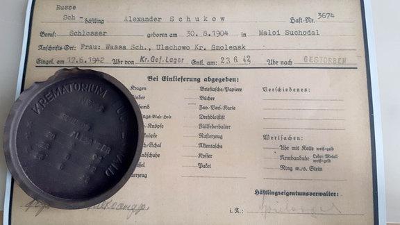 Der Deckel der Urne von Alexander Schukow liegt auf einem Dokument.