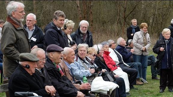 Ältere sitzende Zuschauer der Zeremonie, teilweise mit Kopfhörern für Übersetzung sowie weitere stehende Besucher