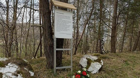 Blumengebinde mit Schleifen vor Erinnerungstafel für KZ-Häftlinge