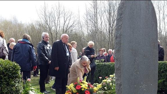 Menschen legen Blumen und Gebinde am Fuß einer übermannshohen Steintafel nieder