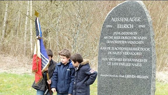 Drei Jungen mit einer auf den Boden gestellten Fahne stehen neben einer hohen Steintafel mit einer Erinnerungsinschrift für die Häftlinge des KZ-Außenlagers