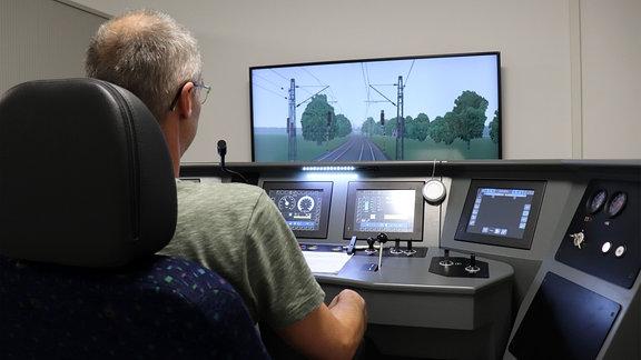 Ein Mann sitzt an einem Simulator eines Führerstandes einer Lok.