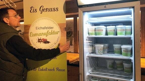 Mann mit Aufsteller Eismanufaktur neben Kühlschrank.