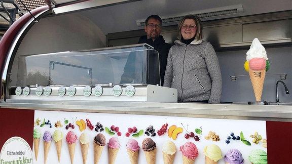 Zwei Personen stehen hinter der Theke in einem Eiswagen.