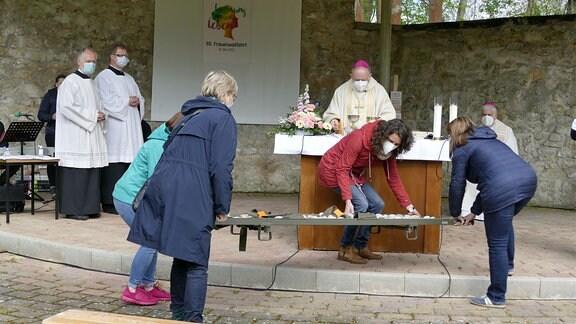 eine Trage mit Steinen wird von Frauen zum Altar gebracht
