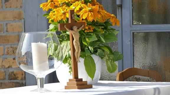 Jesus-Kreuz und Blumenstrauß auf Tisch