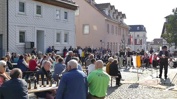 Viele Menschen sitzen an Bierbänken auf der Straße