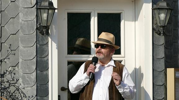Ein Mann mit Hut und Sonnenbrille mit Mikrofon