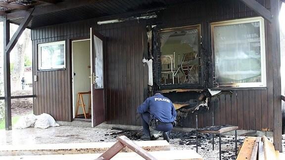 Ein Polizist begutachtet ein Bungalow mit Brandschäden