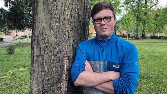 Tom Schieke aus Bleicherode lehnt an einem Baumstamm und setzt sich für queere Jugendliche aus Nordthüringen ein.