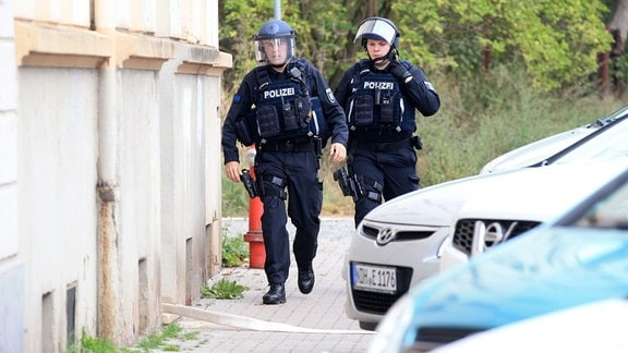 Zwei Polizisten in Schutzkleidung vor einem Haus