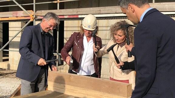Vier Personen schlagen Nägel in einen Holzbalken.
