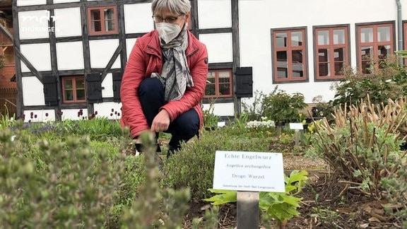 Eine Frau kniet im Apothekergarten in Bad Langensalza.